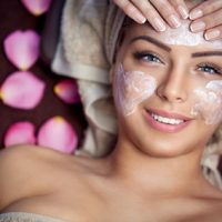 Smiling young woman on spa treatment with facial mask